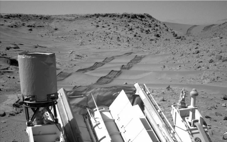 "NASA's Curiosity Mars rover used the Navigation Camera (Navcam) on its mast to catch this look-back eastward at wheel tracks from driving through and past ""Dingo Gap"" inside Gale Crater."