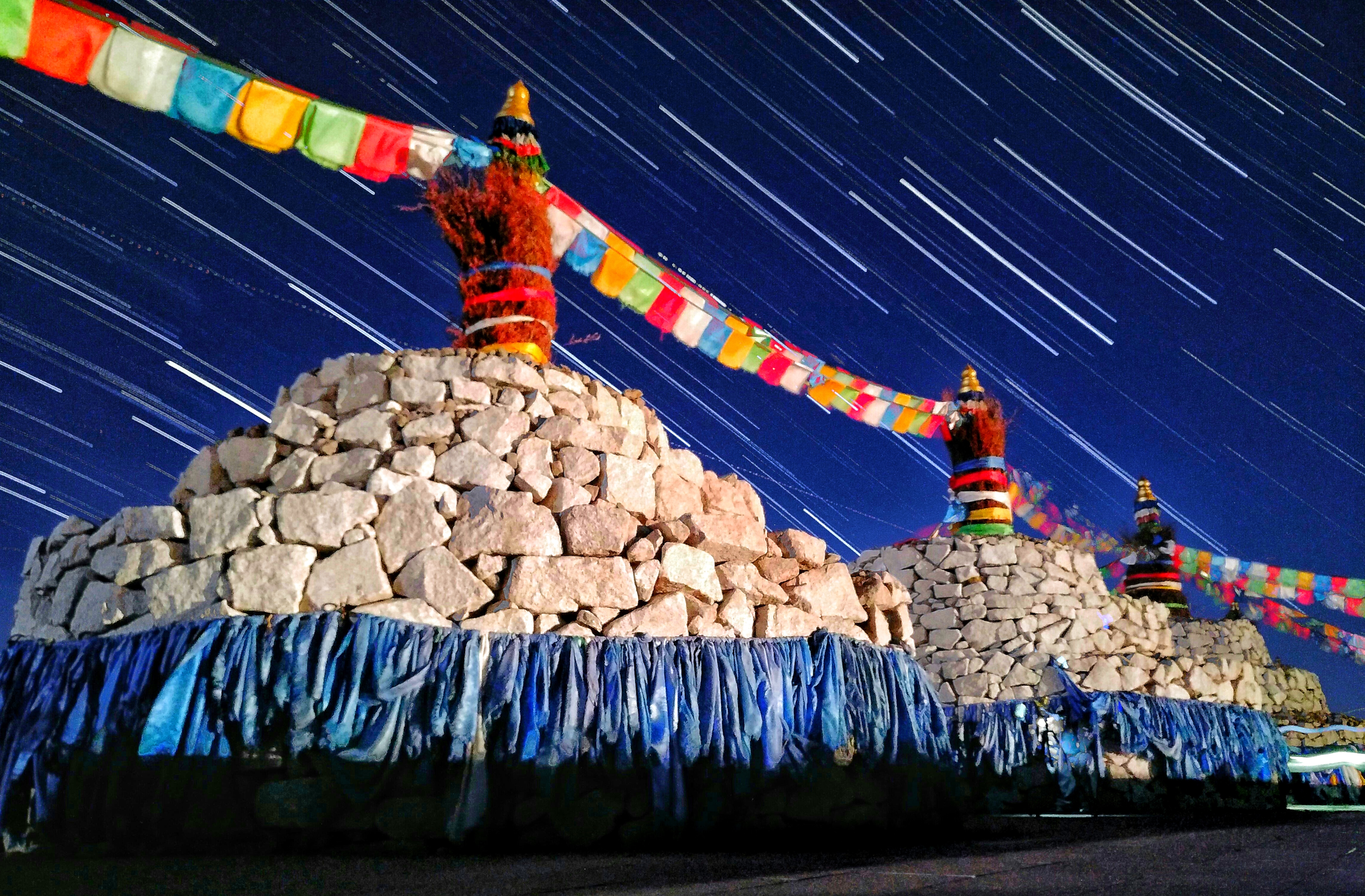 Star trails sweep over colourful and extraordinary sacred altars, called Ovoo, in Mingantu in Inner Mongolia.