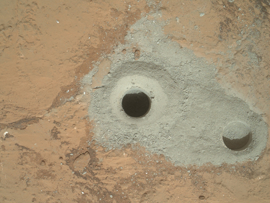 "Image from NASA's Curiosity rover, a hole called ""John Klein"" where the rover conducted its first sample drilling on Mars. Credit: NASA."